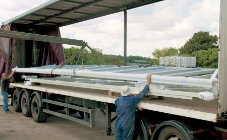 A pair of 11.5m sliding gates painted in light grey being loaded up for an airport.